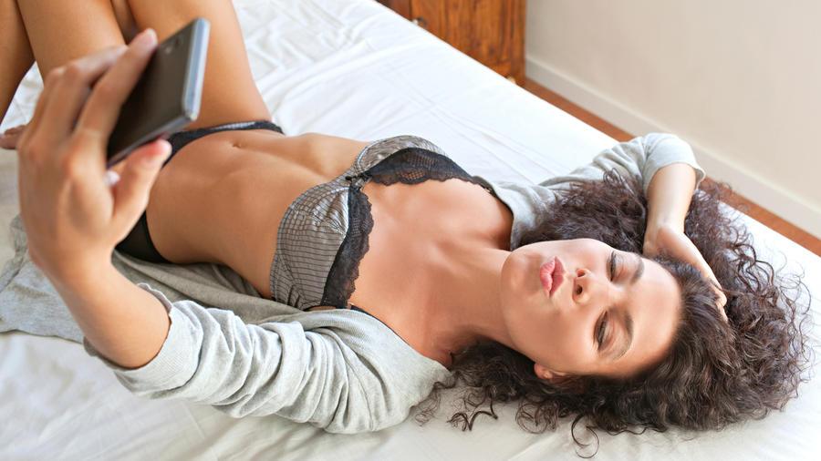Mujer se toma selfie en la cama con lencería