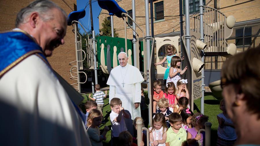 El sacerdote Dave Fitz-Patrick observa a niños reunidos en un patio alrededor de la figura en tamaño natural del papa Francisco en la escuela católica Our Lady of Victor en Washington, el martes 8 de septiembre de 2015, durante un ensayo de un acto para l