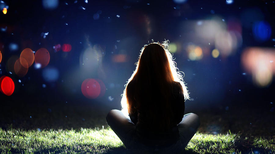 mujer de espaldas sentada sobre la hierba de noche