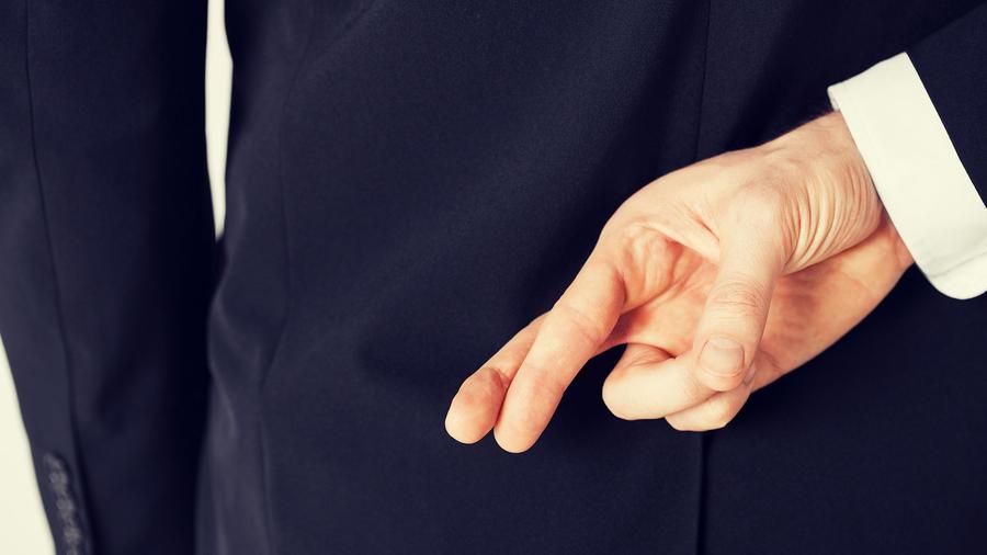 Hombre con saco azul cruzando los dedos detrás de la espalda