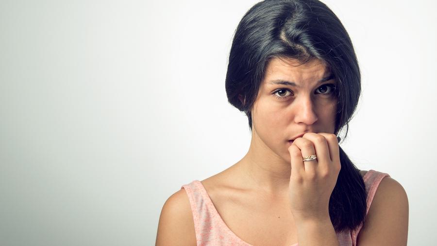 Mujer morena con blusa rosa mordiéndose las uñas