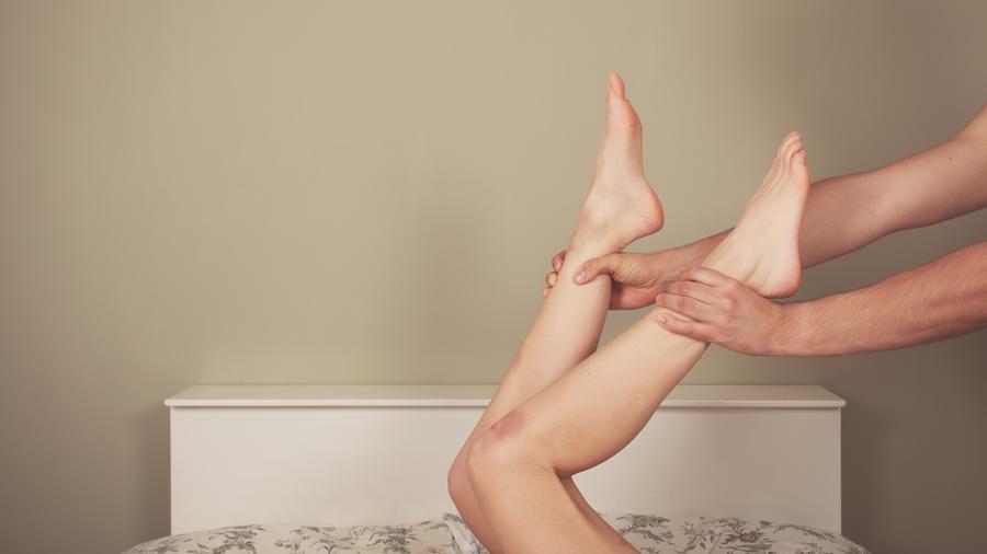 Manos de hombre sujetando las piernas de una mujer en la cama