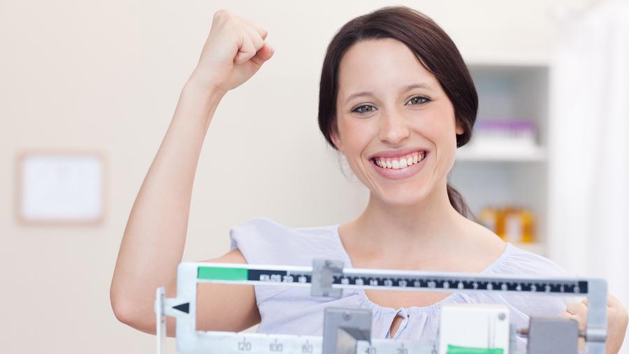 Mujer feliz sobre una balanza