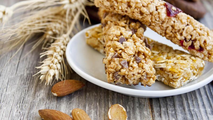 Tres barritas de cereal sobre un plato blanco, junto a almendras y trigo