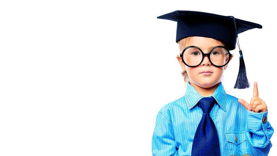 Niño pequeño con camisa y corbata y birrete de graduado