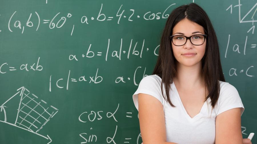 Mujer con lentes vestida de blanco frente a un pizarrón con ecuaciones