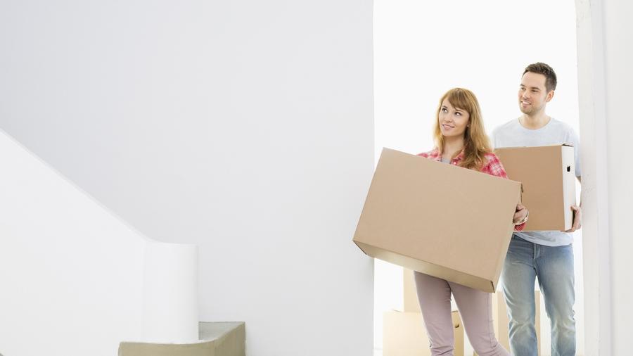Pareja entrando a una casa sosteniendo una caja de cartón cada uno