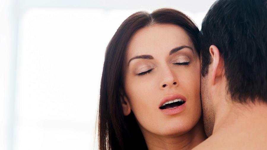 Mujer disfrutando mientras un hombre la besa