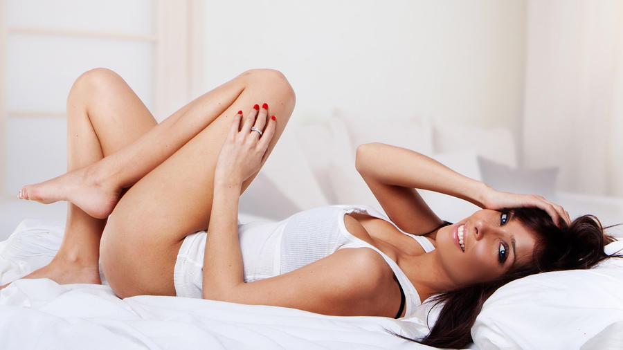 Mujer en la cama sosteniéndose la cabeza