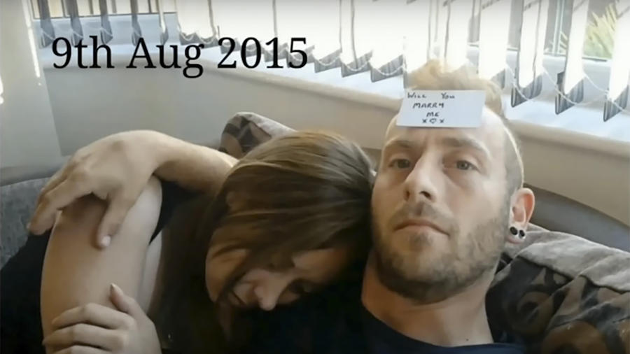 Ray Smith con un cartel en la frente junto a su novia dormida