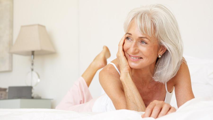 Mujer con cabello blanco en la cama