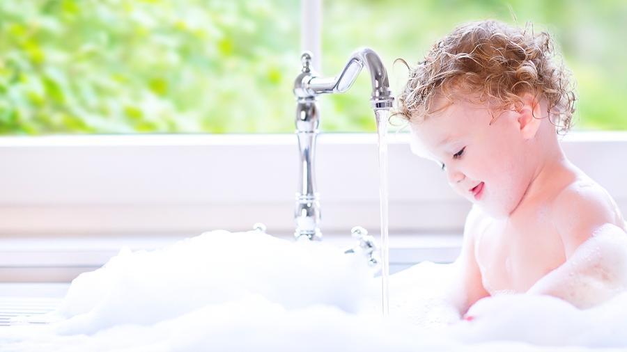 Niño rubio dentro de una tina de baño