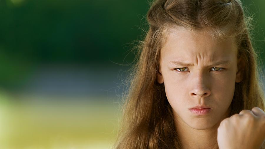 Joven de pelo castaño con cara de enojada y empuñando una mano
