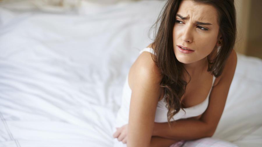 Mujer con ropa blanca con cólicos en la cama