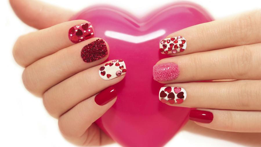 Mujer sosteniendo un corazón rosa con manicure de corazones