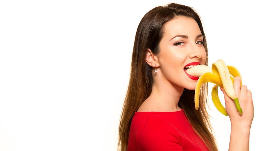 Mujer con blusa roja comiendo una banana