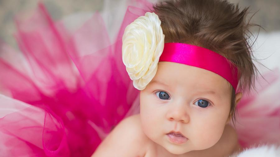 Bebé con flor en la cabeza y cinta rosa