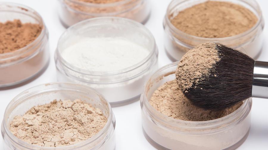 Frascos de polvos de maquillaje y brocha