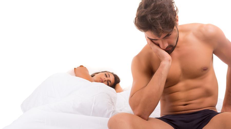 Hombre sentado al borde de la cama pensativo junto a una mujer dormida