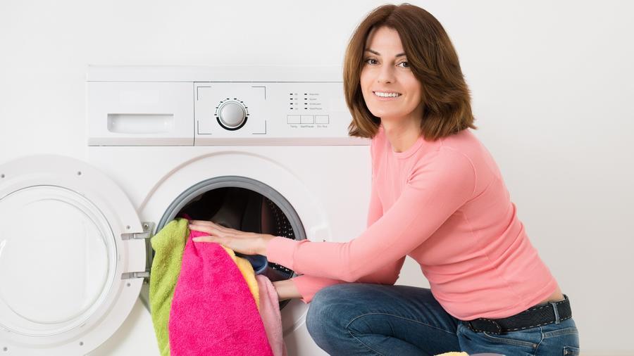 Mujer con blusa rosa y pantalón de mezclilla poniendo ropa a lavar
