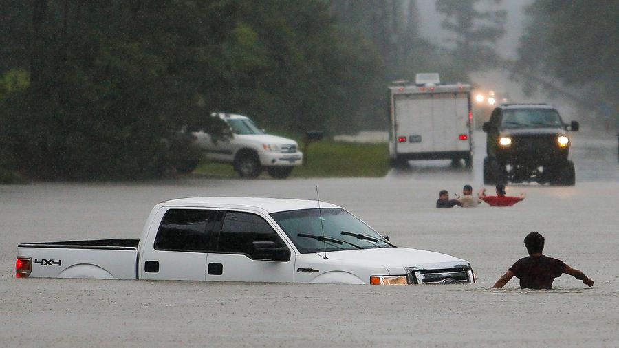 Un hombre trata de asegurarse de que los tres ocupantes de una camioneta escaparon a salvo luego que el vehículo quedase varado en una crecida en Nichols Sawmill Road el viernes, 27 de mayo del 2016, en Magnolia,Texas
