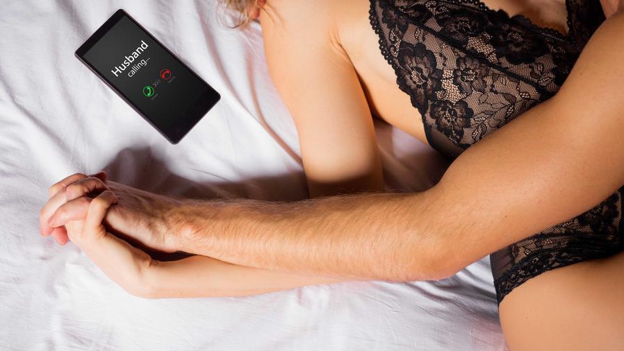 Pareja en la cama agarrados de manos con celular al lado