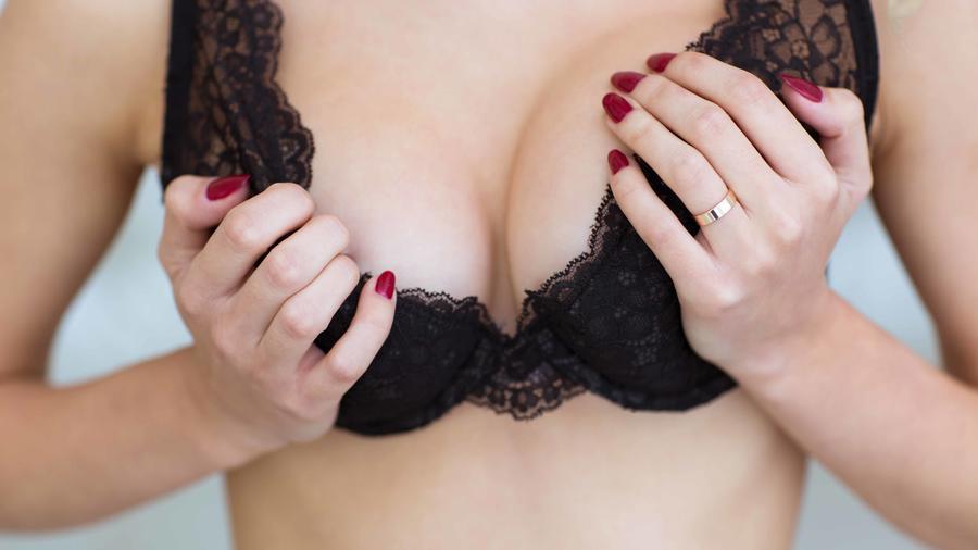 Mujer con sujetador negro apretándose los pechos