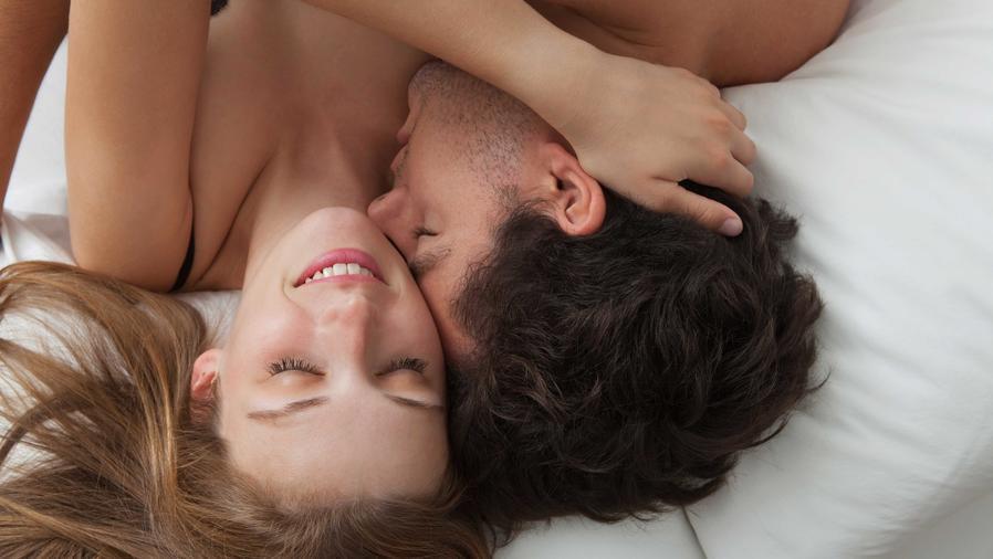 Hombre besa en el cuello a mujer, acostados sobre la cama