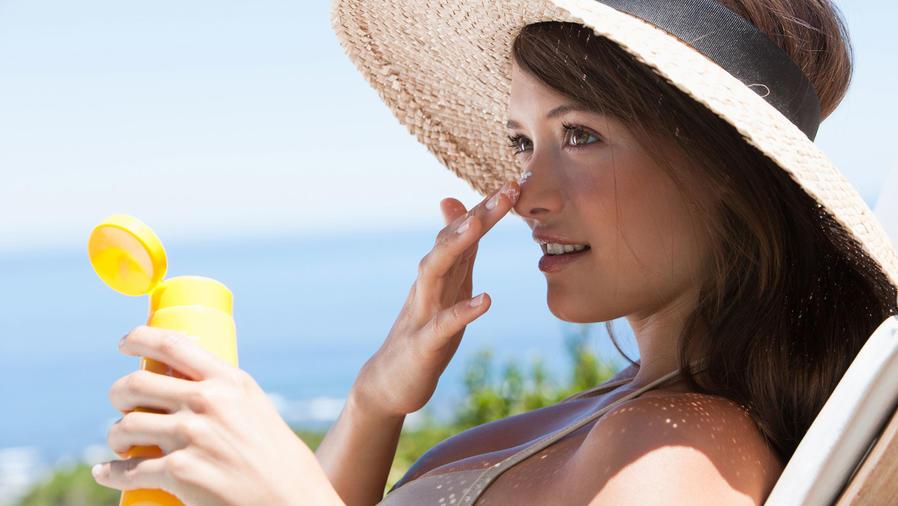 Mujer con sombrero aplicándose bloqueador solar
