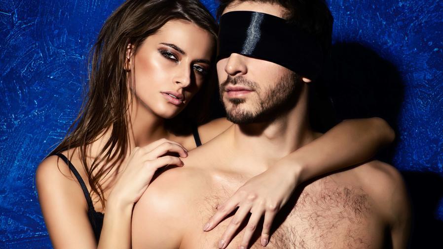 Mujer abrazando por la espalda a un hombre con los ojos vendados