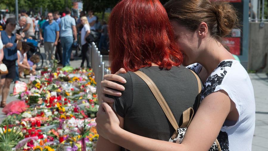 Unas personas acuden al centro comercial Olympia donde un hombre armado mató a nueve personas hace dos días, en Múnich, Alemania, el domingo 24 de julio de 2016