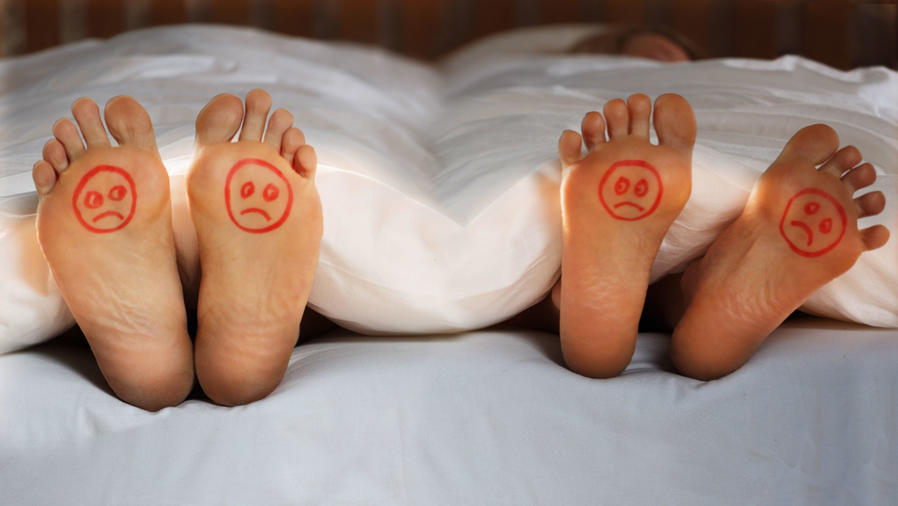 Feet at end of bed with sad faces drawn on