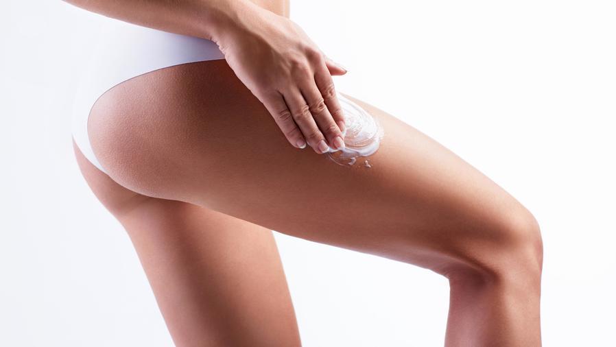 Mujer aplicándose crema en el muslo