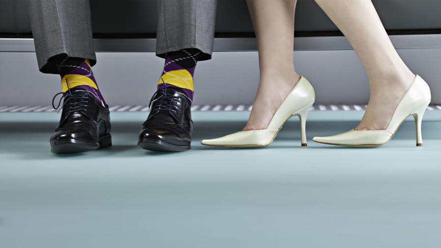 Pies de hombre con medias rayadas y pies de mujer con zapatos blancos