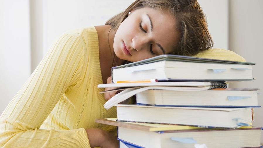 Mujer joven dormida en su banco sobre una pila de libros