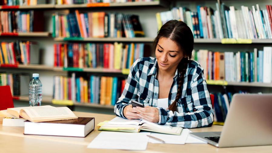 Estudiante universitaria con Smartphone en biblioteca