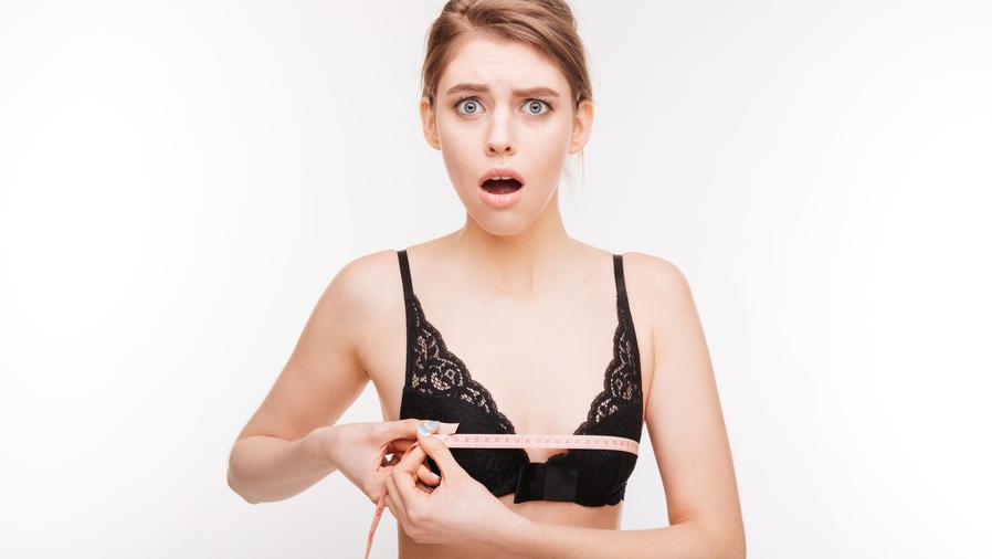 Chica con cara de sorprendida midiendo el tamaño de sus pechos
