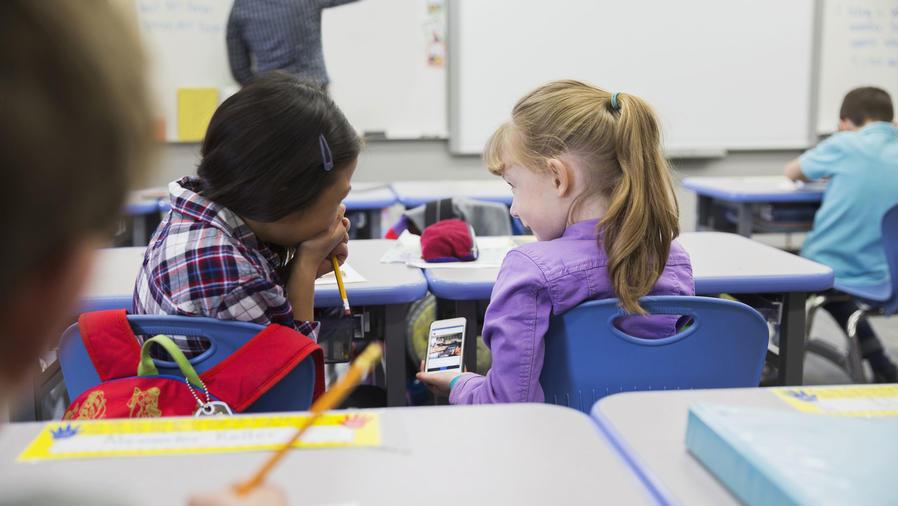 Niñas de primaria riendo con su móvil en clase
