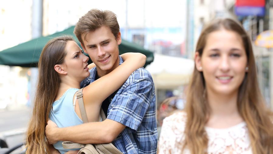 Hombre abrazando a su novia y mirando a otra chica