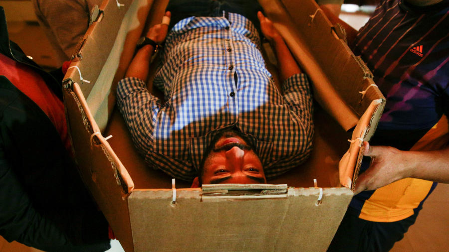 Elio Angulo lies inside a cardboard coffin as he introduces his product to potential customers at a mortuary in Valencia