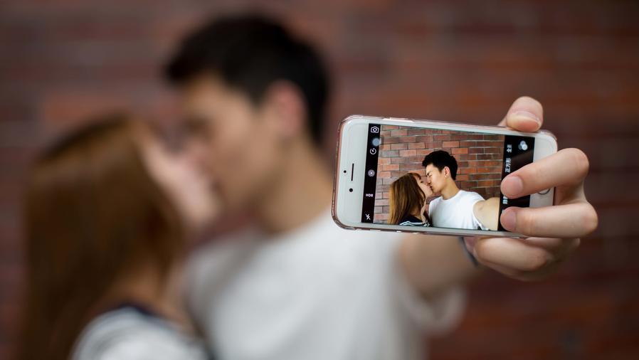 Pareja besándose y tomándose un selfie a la vez