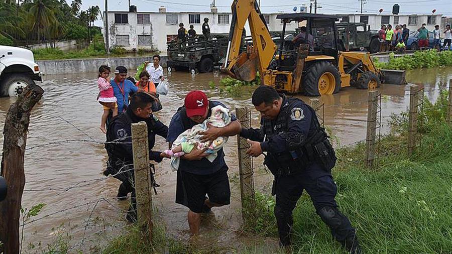 Integrantes de la Policía Estatal de Guerrero evacuando a damnificados por el desborde del río La Sabana en Guerrero, México