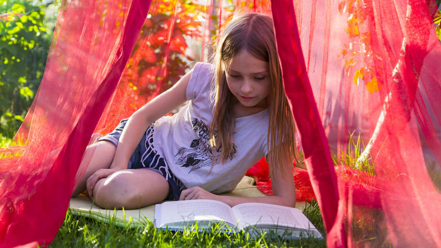Niña leyendo en una tienda de jardín rosa