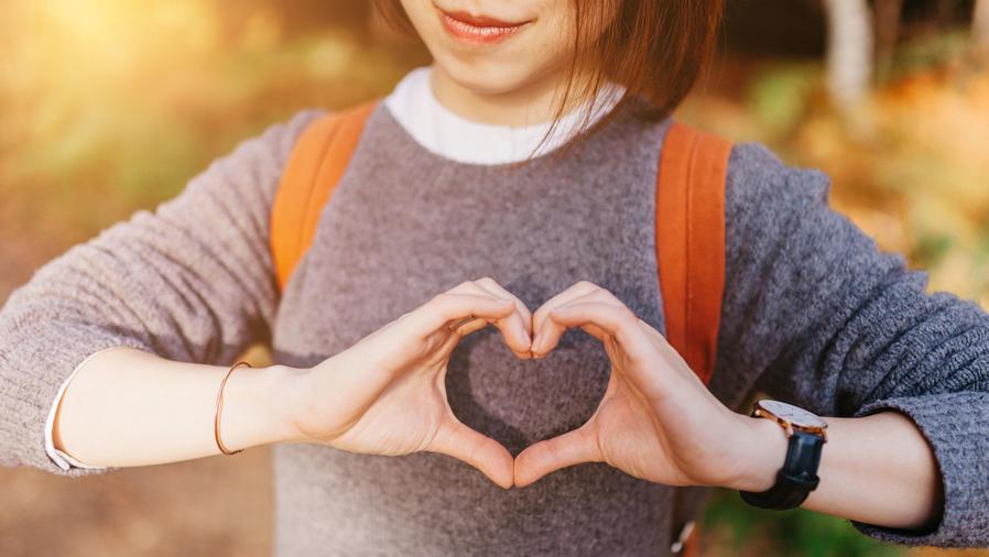 Acercamiento a una mujer formando un corazón con las manos