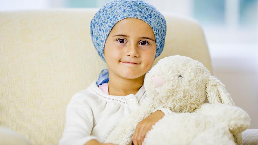 Niña con cáncer con un pañuelo en la cabeza y su conejo de peluche