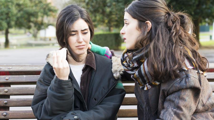 Mujer joven consolando a una amiga
