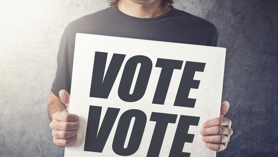 """Hombre sosteniendo un cartel con el lema """"vote"""""""