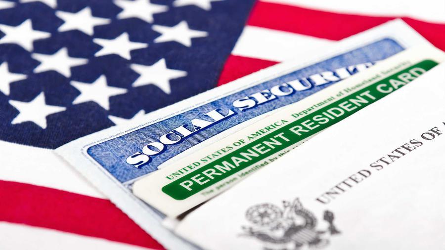 Green Card sobre bandera de Estados Unidos