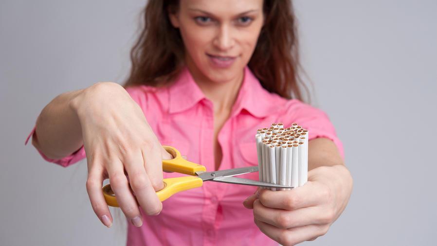 Mujer corta puñado de cigarrillos con tijera