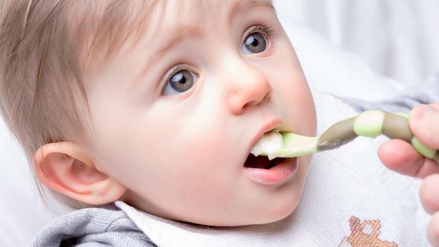 Bebé comiendo con cuchara y babero